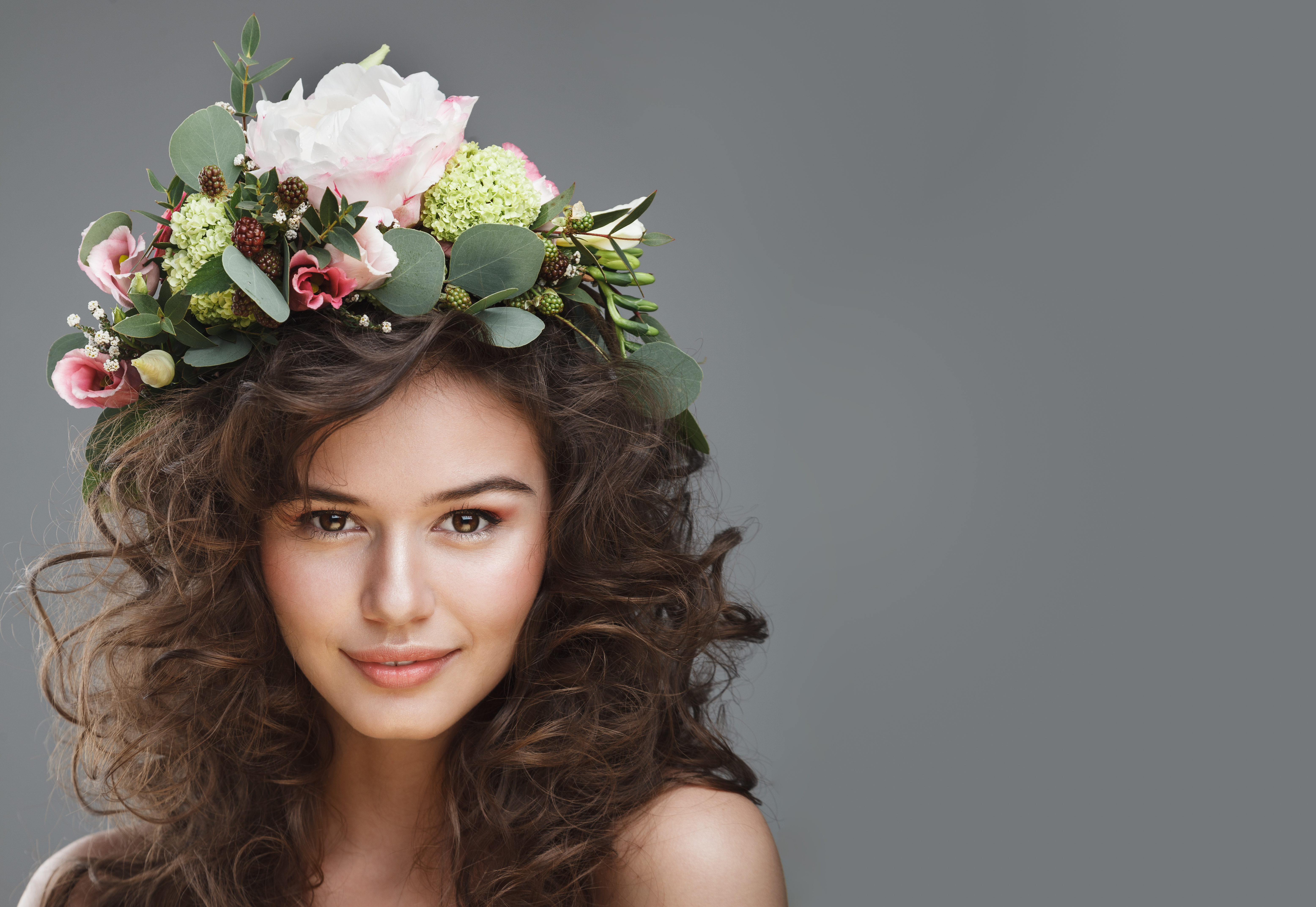 woman with curly brown hair and a flower decoration on top.jpeg