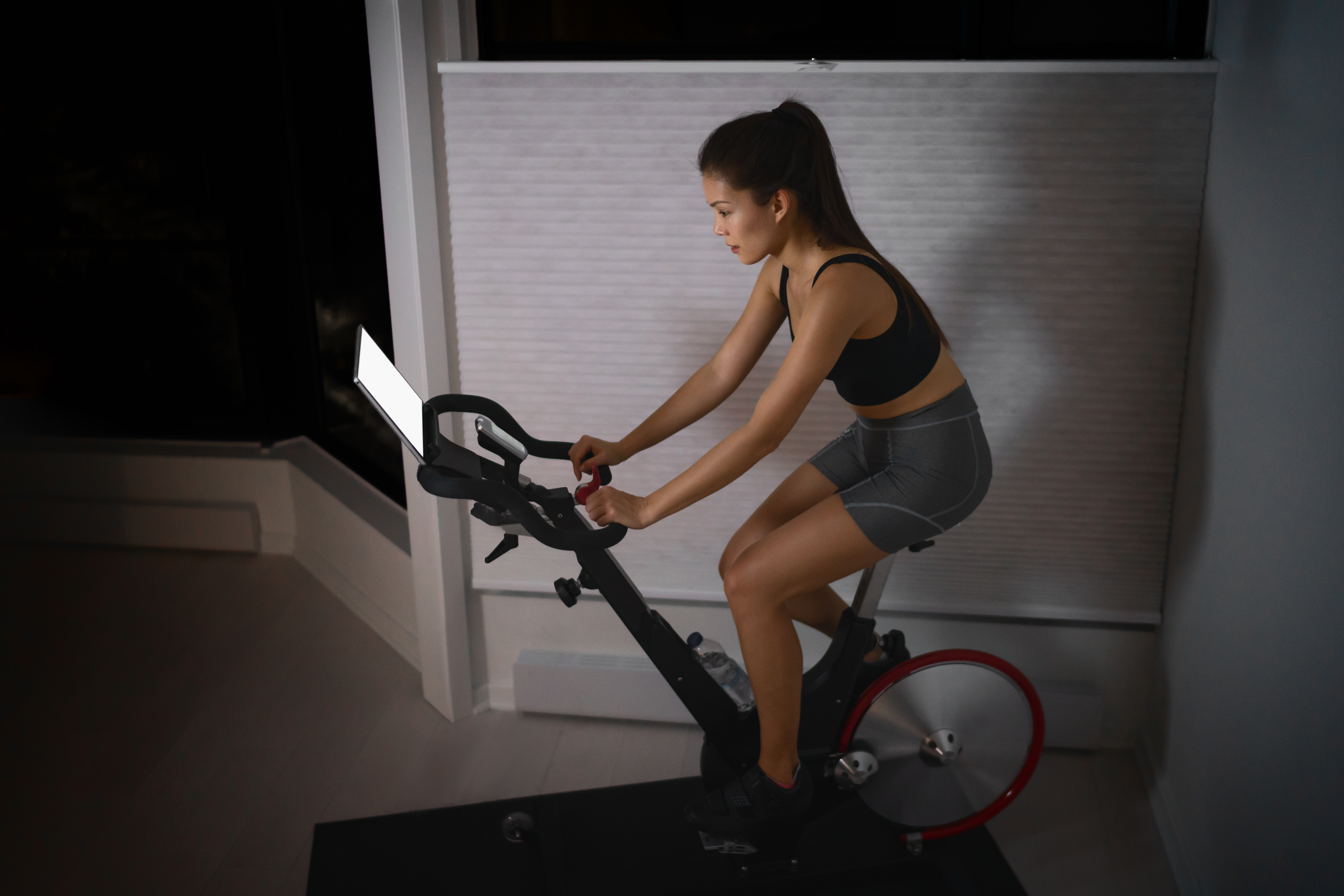 Home workout indoor stationary bike Asian girl biking screen with online classes woman training on smart fitness equipment indoors for cycling exercise. Late at night in bedroom