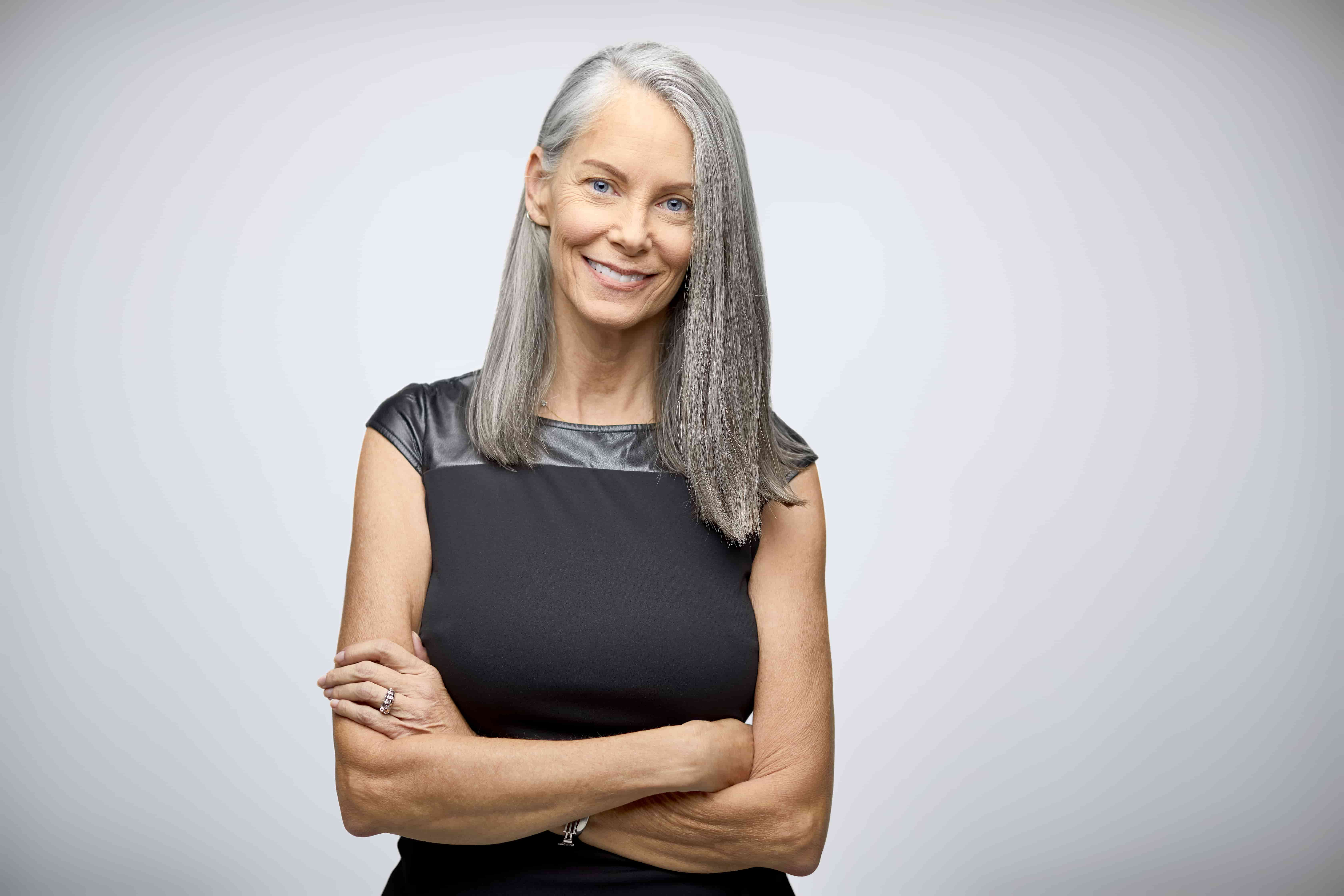 elegant woman with long grey hair smiling to the camera