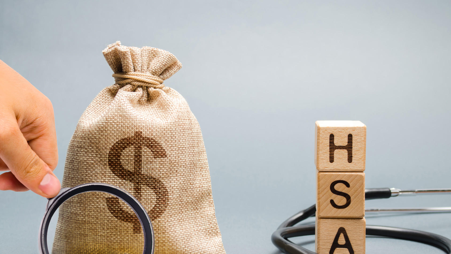 Wooden blocks with the word HSA and money bag with stethoscope. Health savings account. Health care. Health insurance. Investments. Tax-free medical expenses. Coins and dollar sign