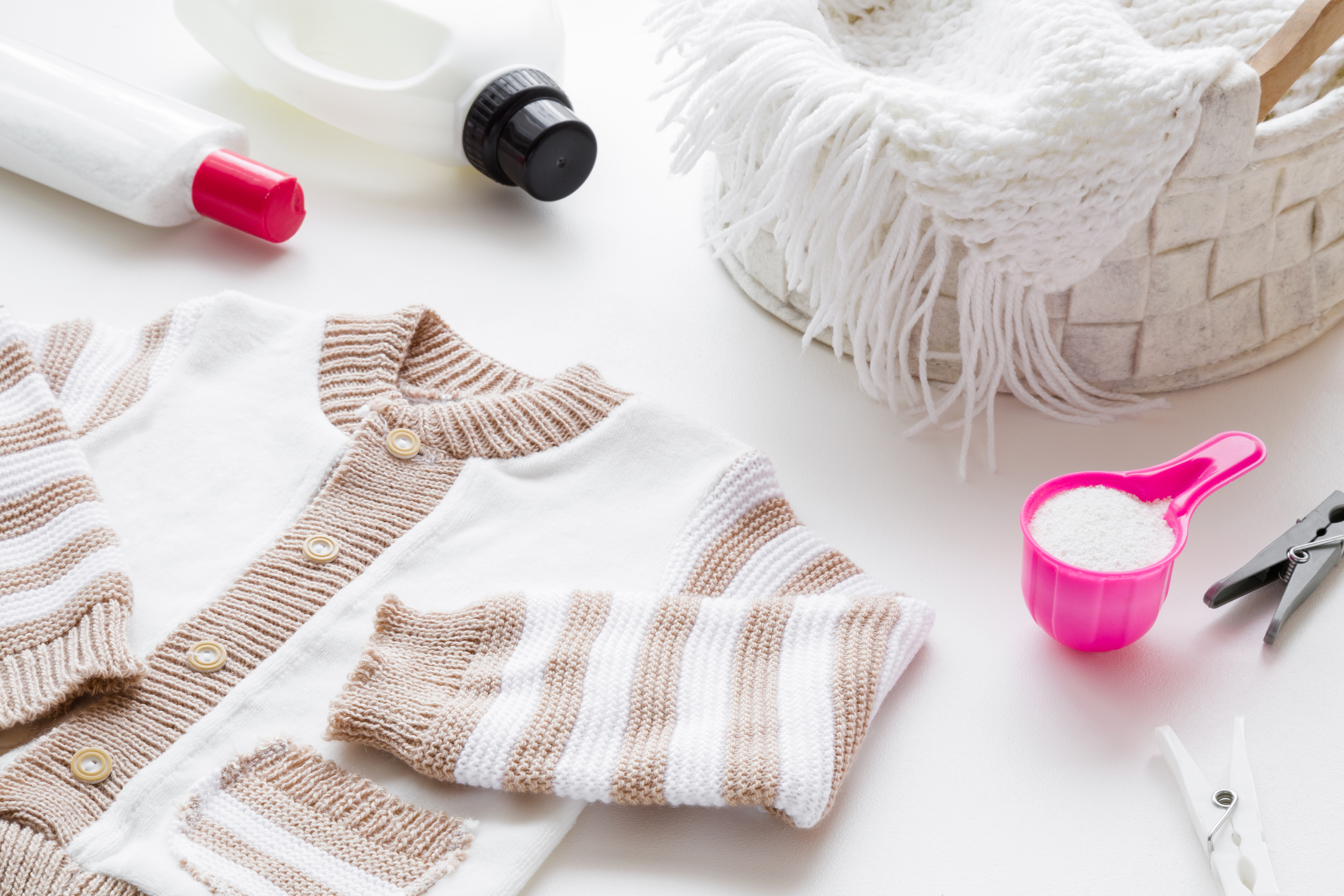 White and light brown, warm child sweater on table. Different washing detergents. Pink cup or scoop of white powder and softener. Regular washing. Mother and father duties.