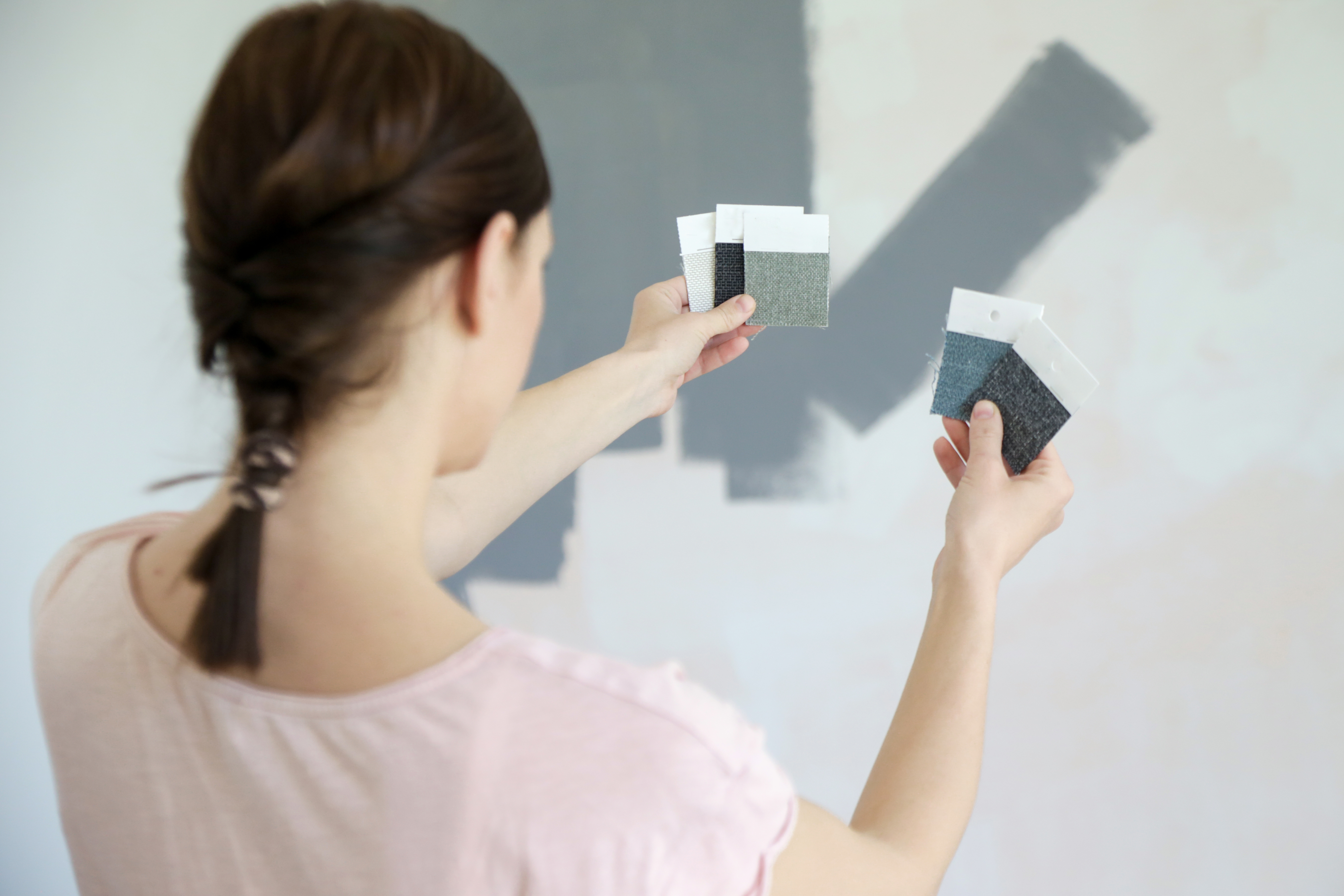 Young women choosing a perfect shade of grey for walls in her new home