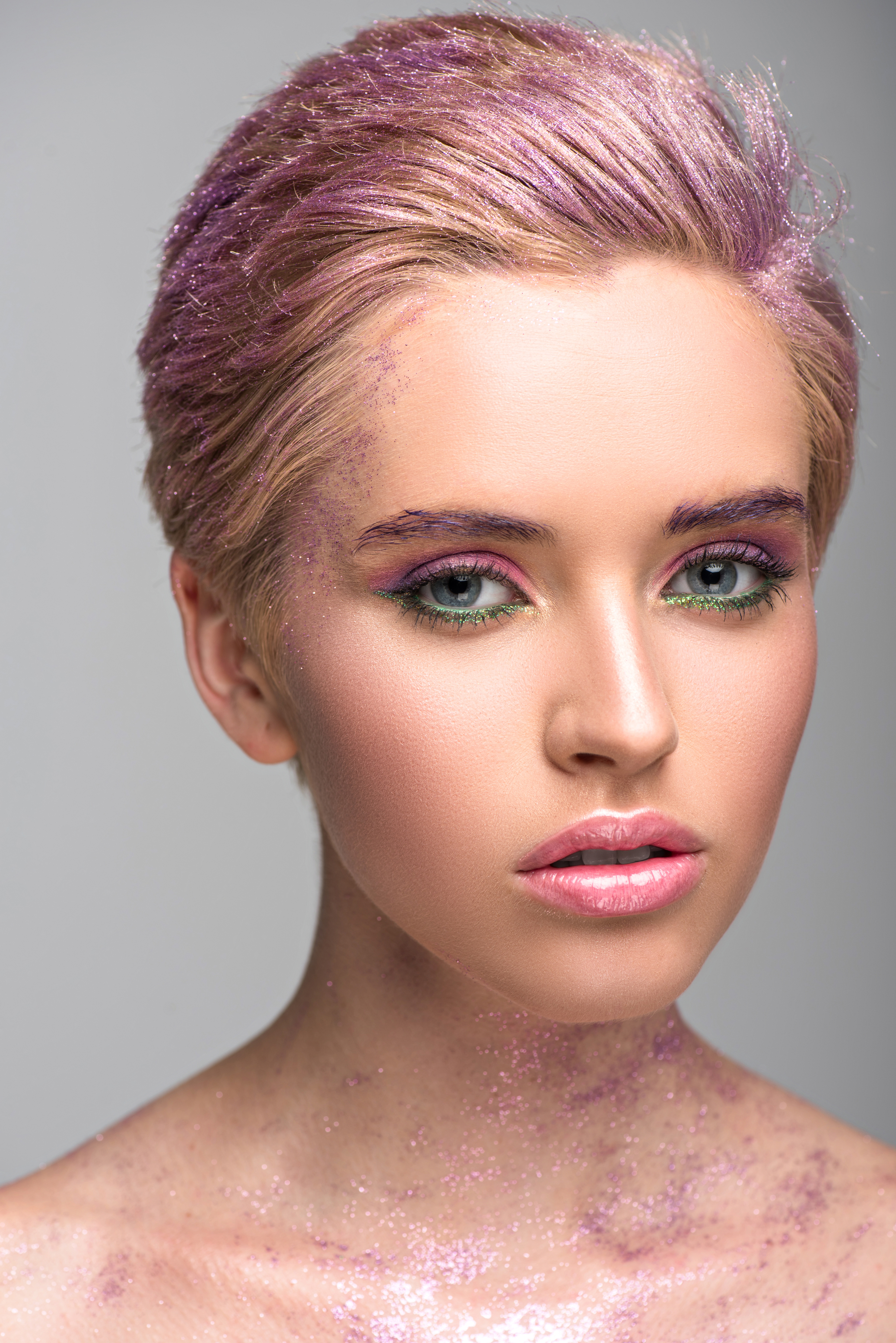 attractive woman with violet glitter on face and hair looking at camera isolated on grey