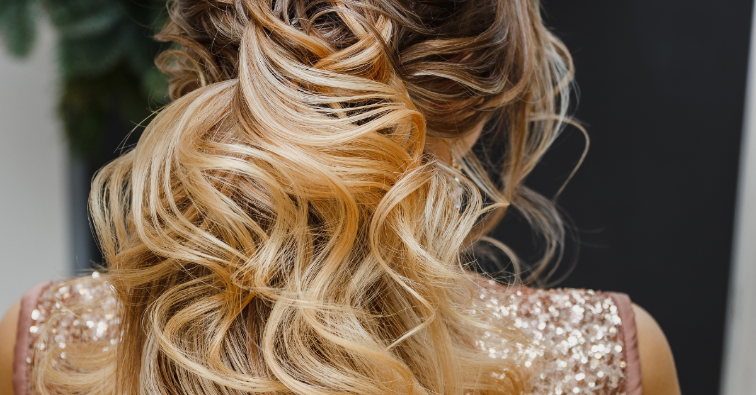 Rear view closeup of a hairdresser masterpiece of wavy and textured tail hairstyle in beauty salon