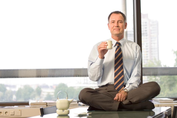 Man sitting on top of desk with tea cup
