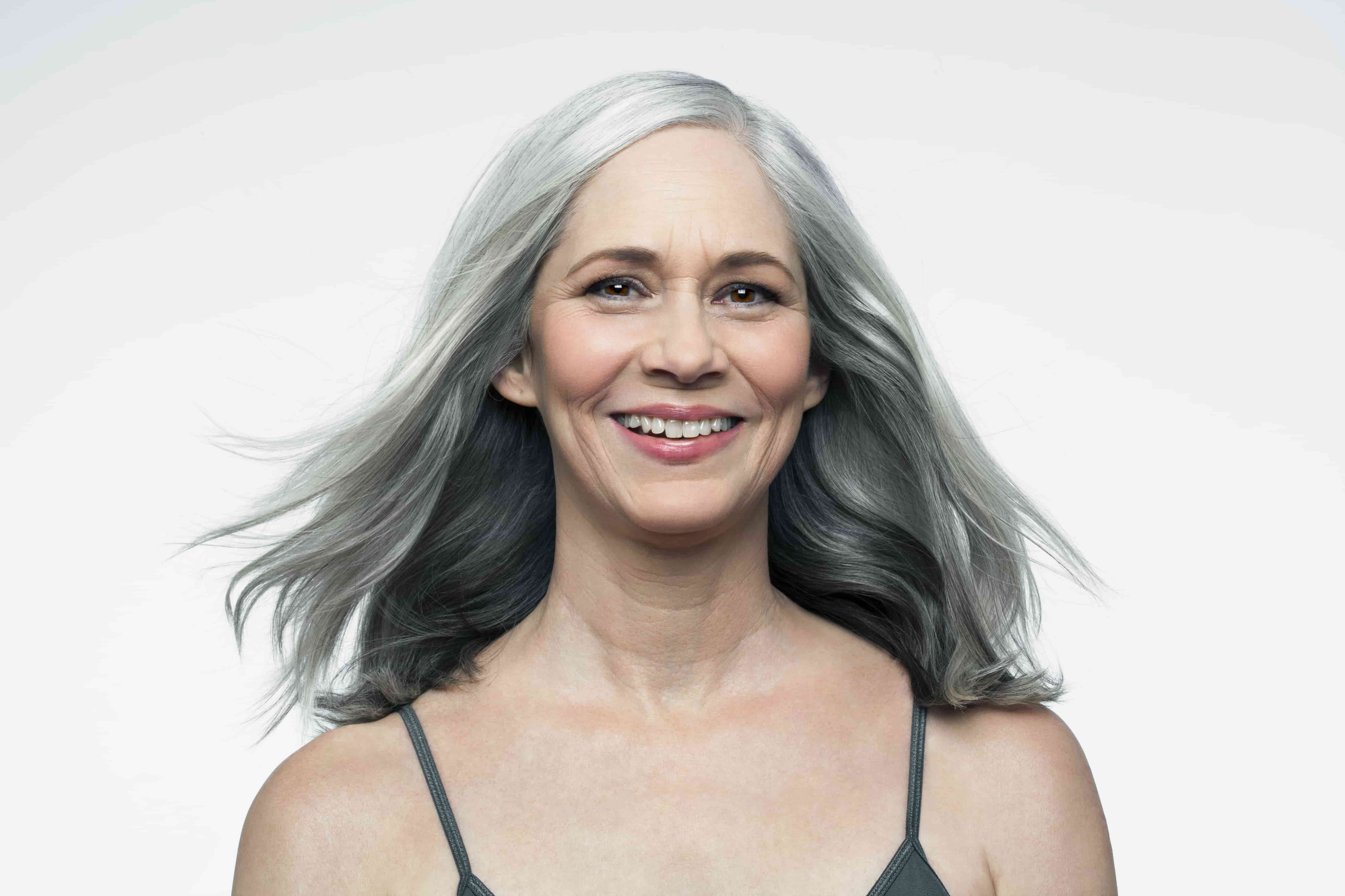 woman with grey hair smiling to the camera