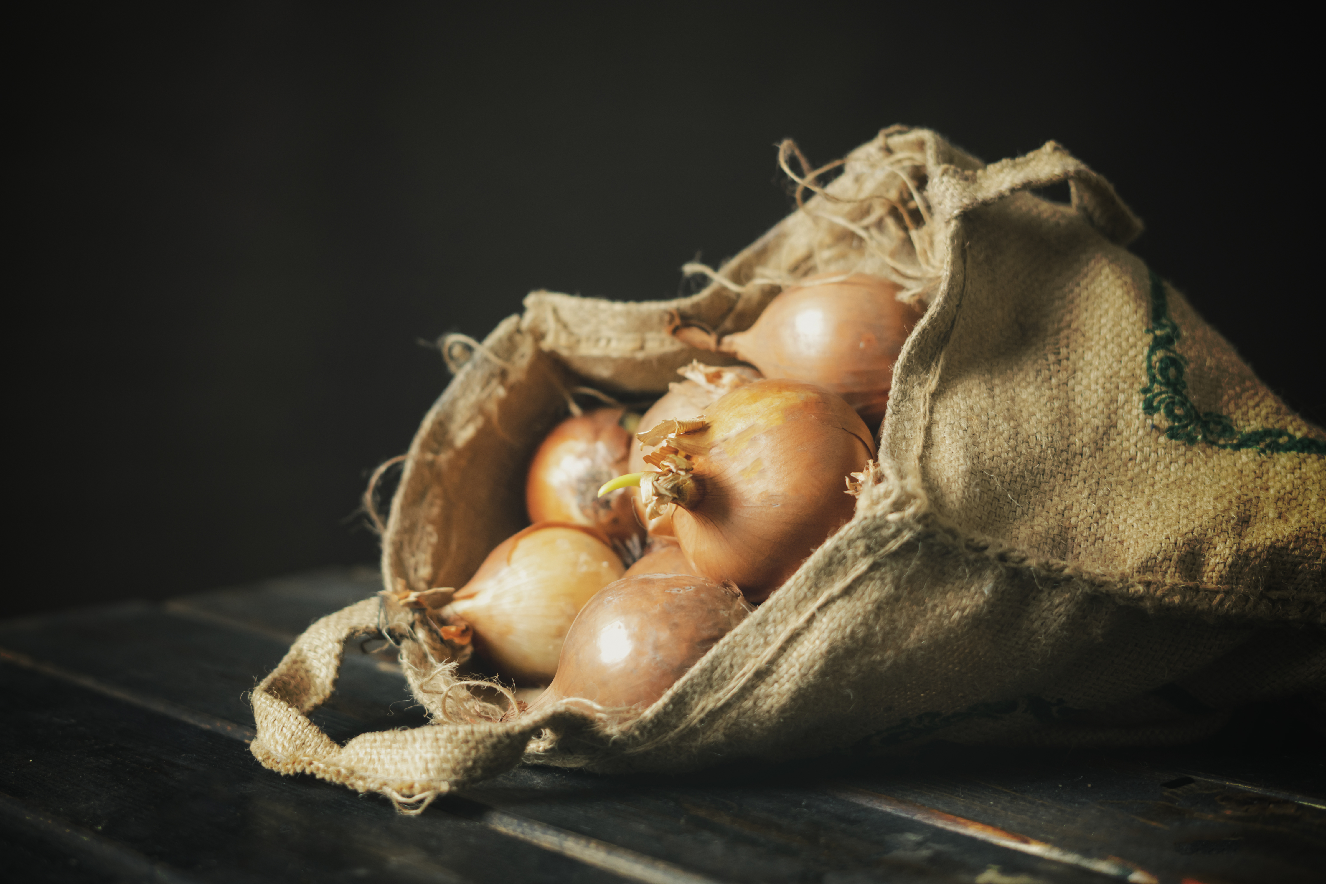 hand hold fresh onion cloth bag isolated on wooden surface b