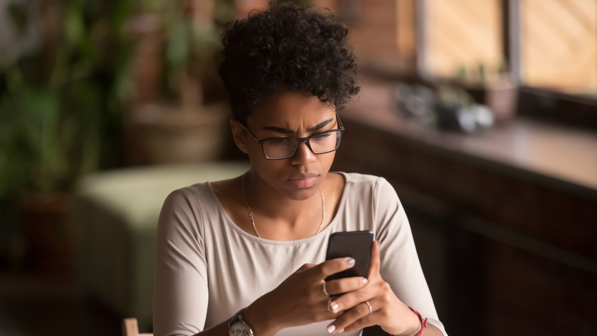 Upset confused african woman holding cellphone having problem with phone