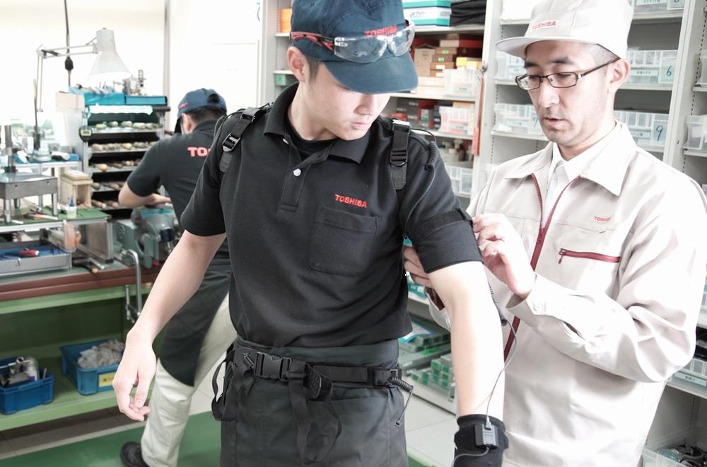 Nakamura helping Okabe put on the motion capture sensors