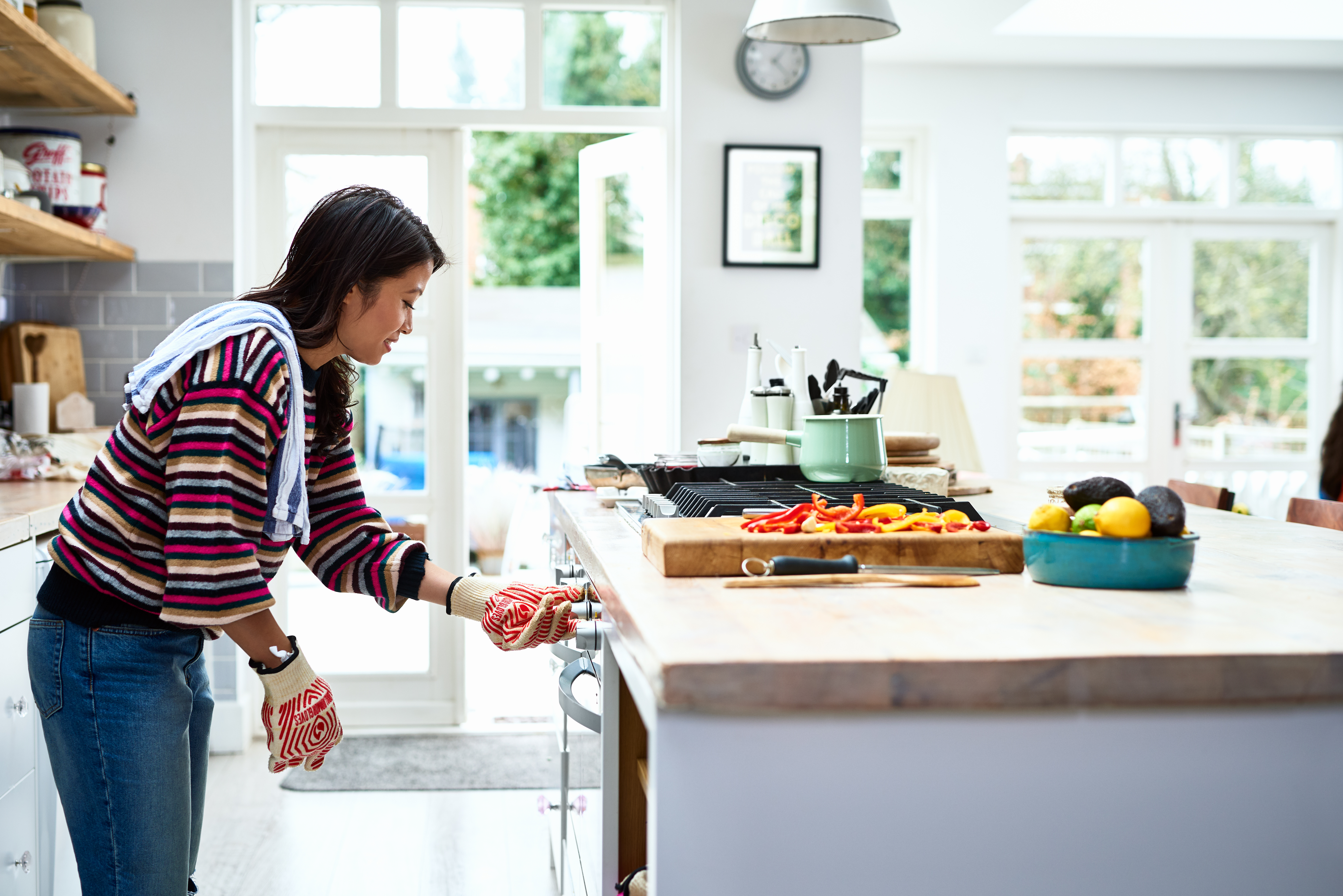 Woman adjusting oven and preparing dinner in kitchen