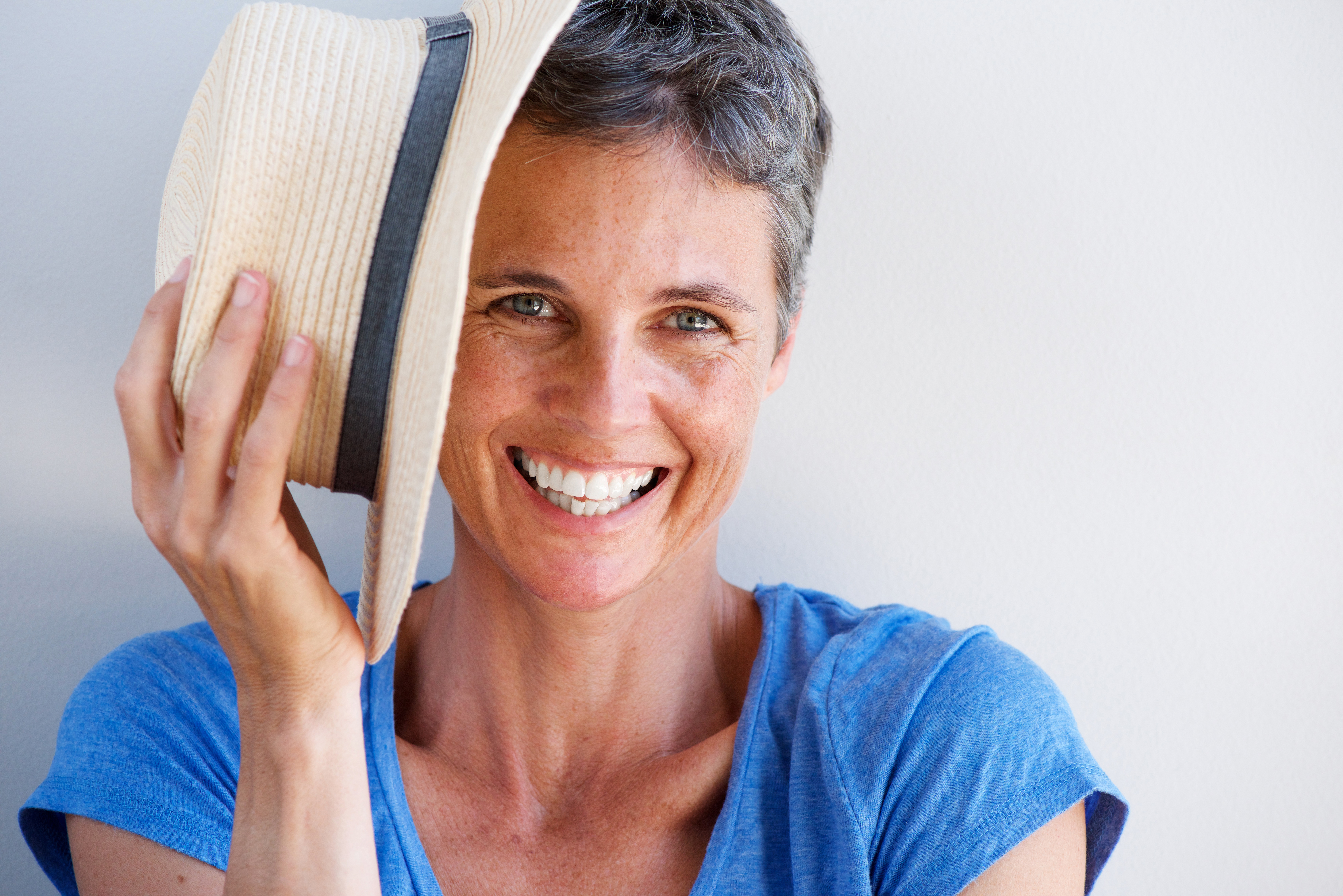 Close up smiling mature woman with hat against white wall
