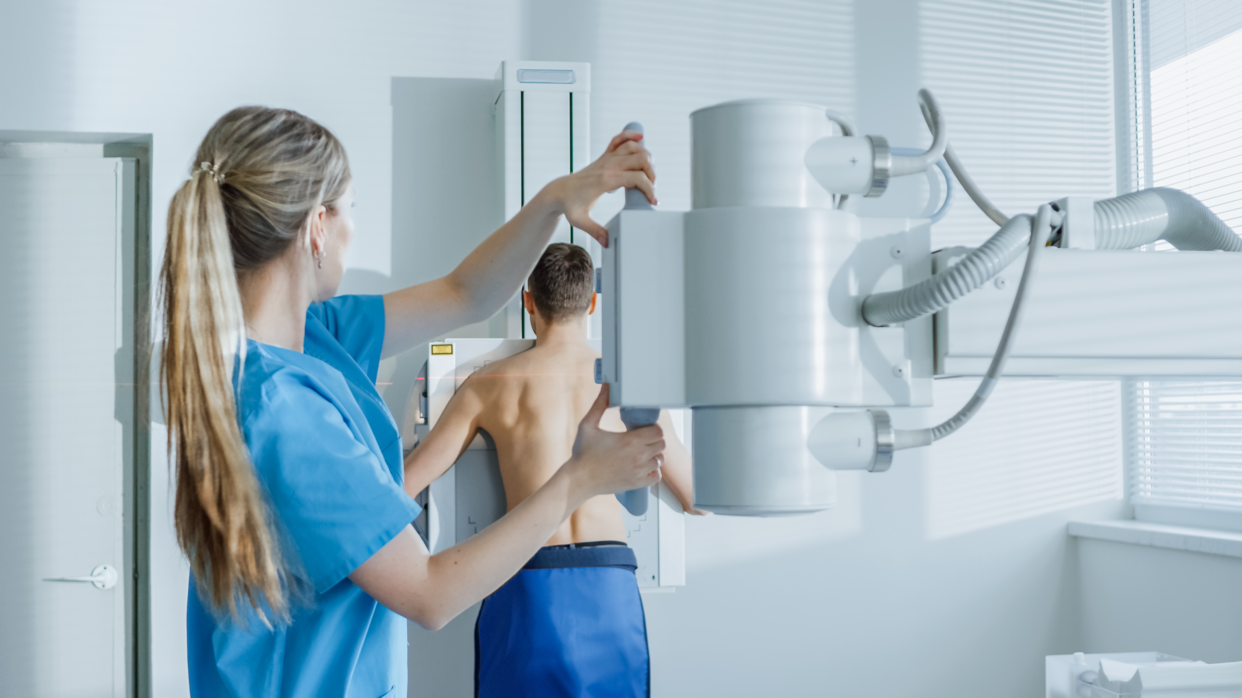 In the Hospital, Man Standing Face Against the Wall While Medical Technician Adjusts X-Ray Machine For Scanning. Scanning for Fractures, Broken Limbs, Chest, Cancer or Tumor. Modern Hospital with Technologically Advanced Medical Equipment.