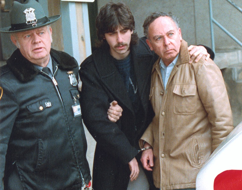 Jesse Friedman puts his arm around his father, Arnold Friedman as they are escorted in handcuffs by police