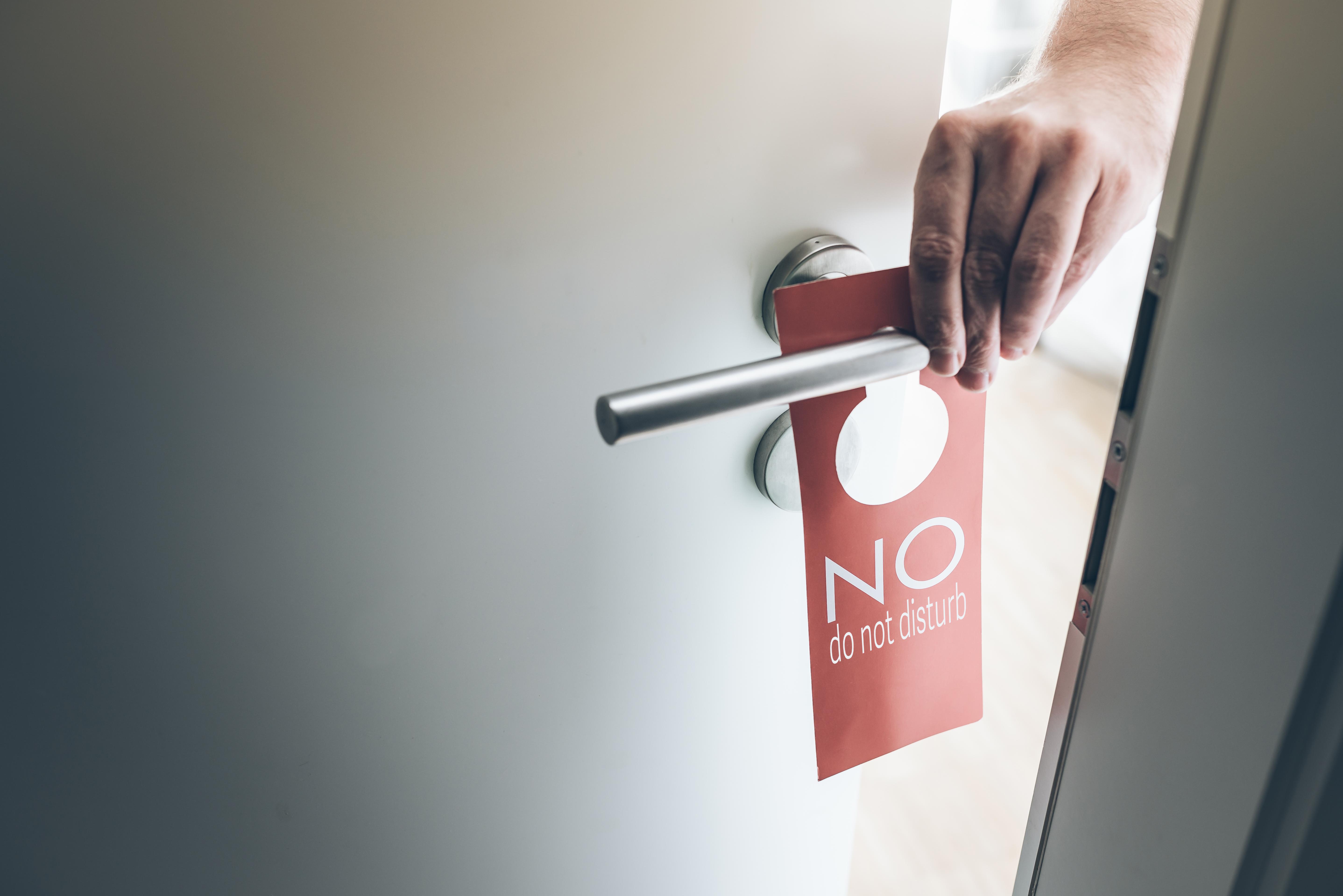 hand placing red do not disturb sign on handle of hotel room door