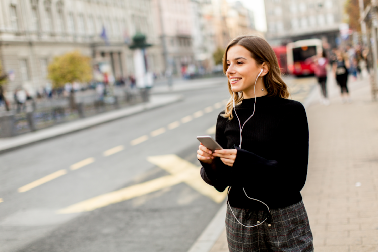 Young brunette woman using mobile while standing on street and  waiting for a bus or taxi