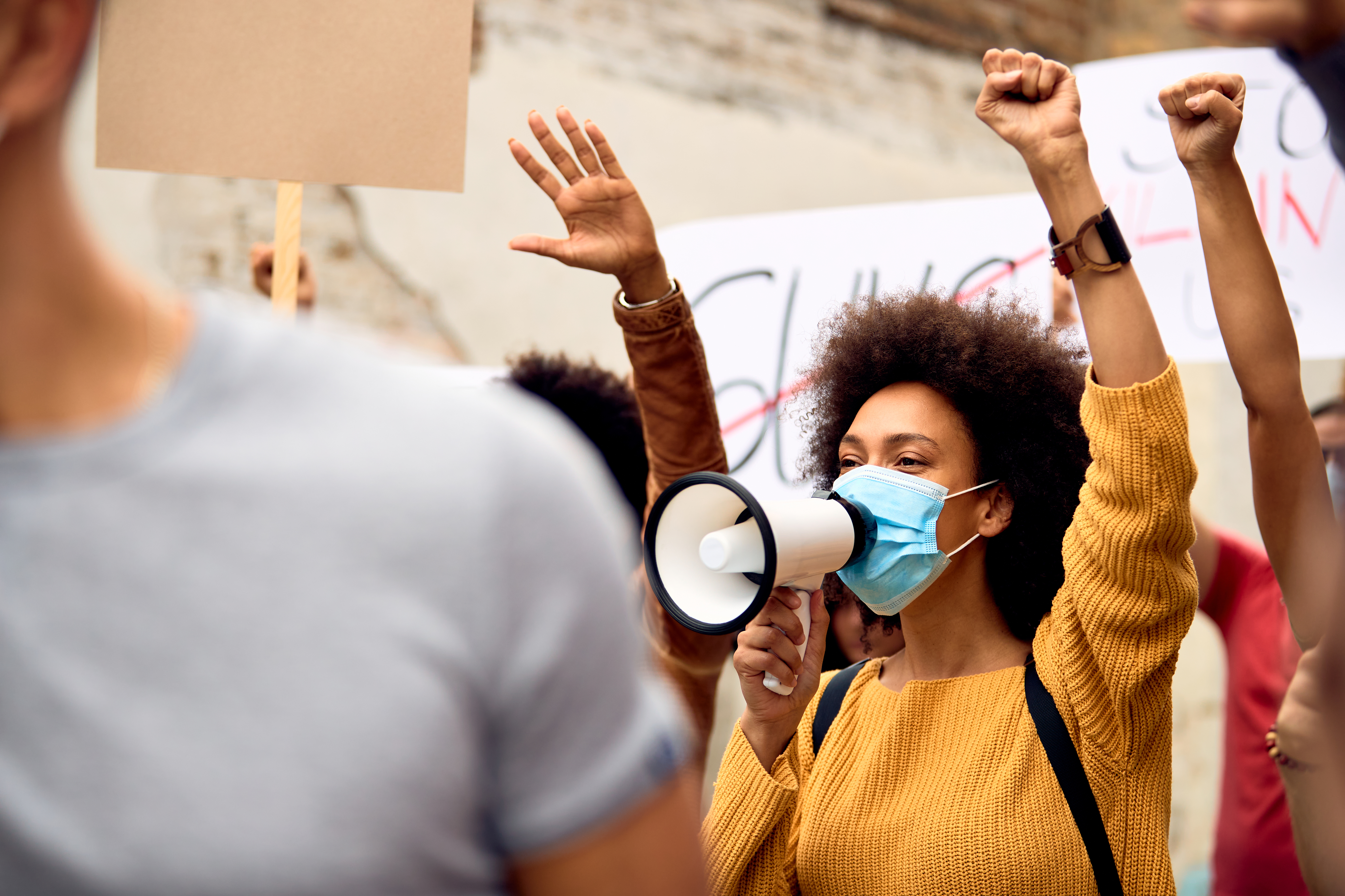 Young black woman wearing protective face mask while shouting through megaphone on anti-racism solidarity protest.