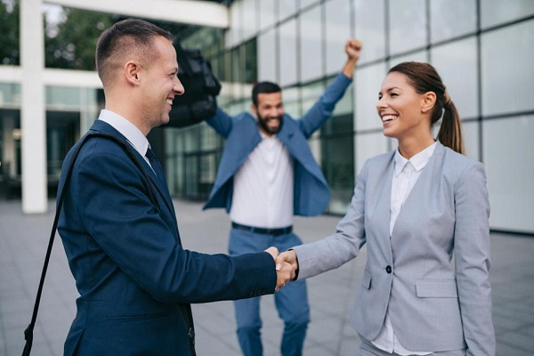 two people shaking hands with excited co-worker behind them