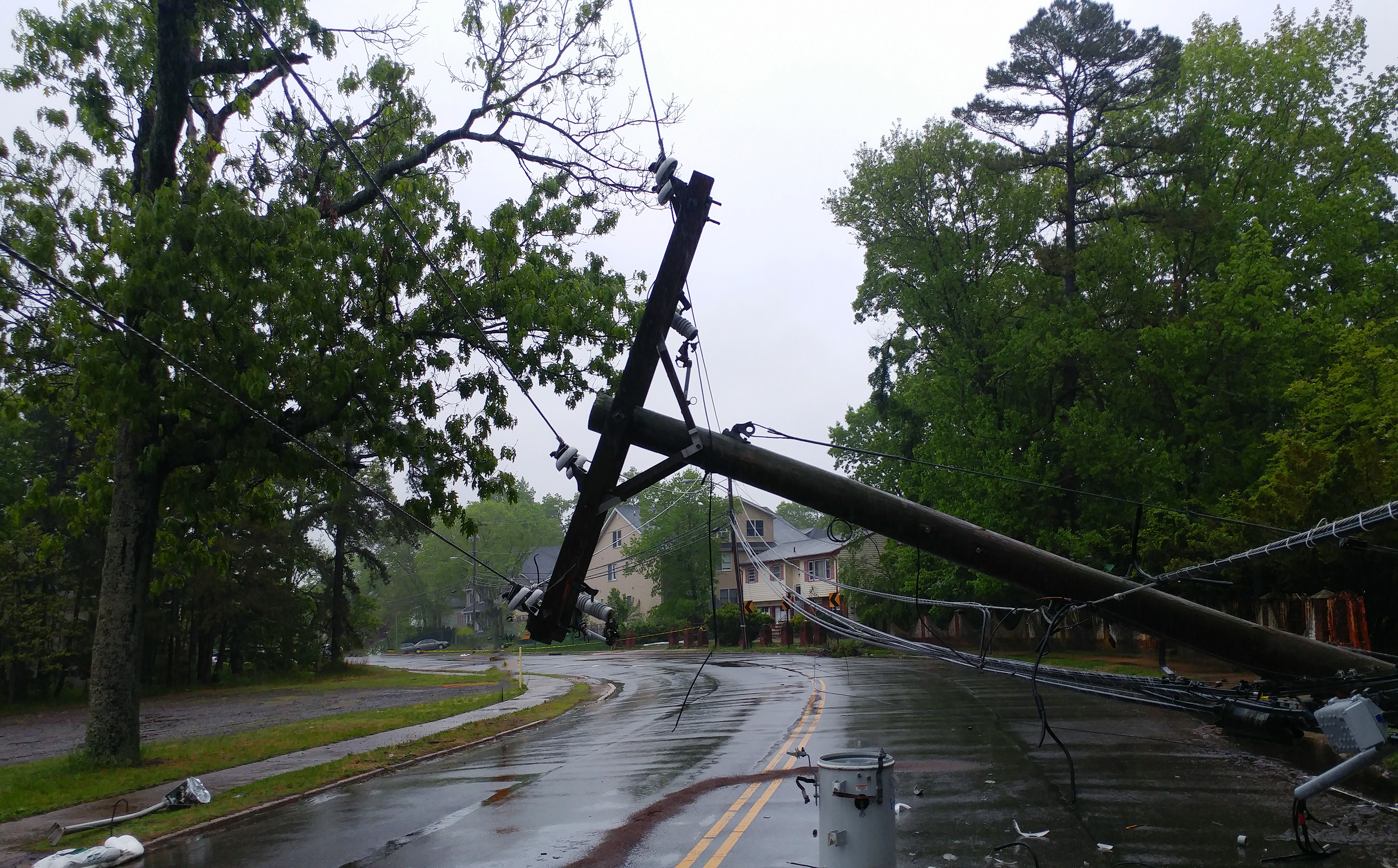 Storm damaged electric transformer on a pole and a tree