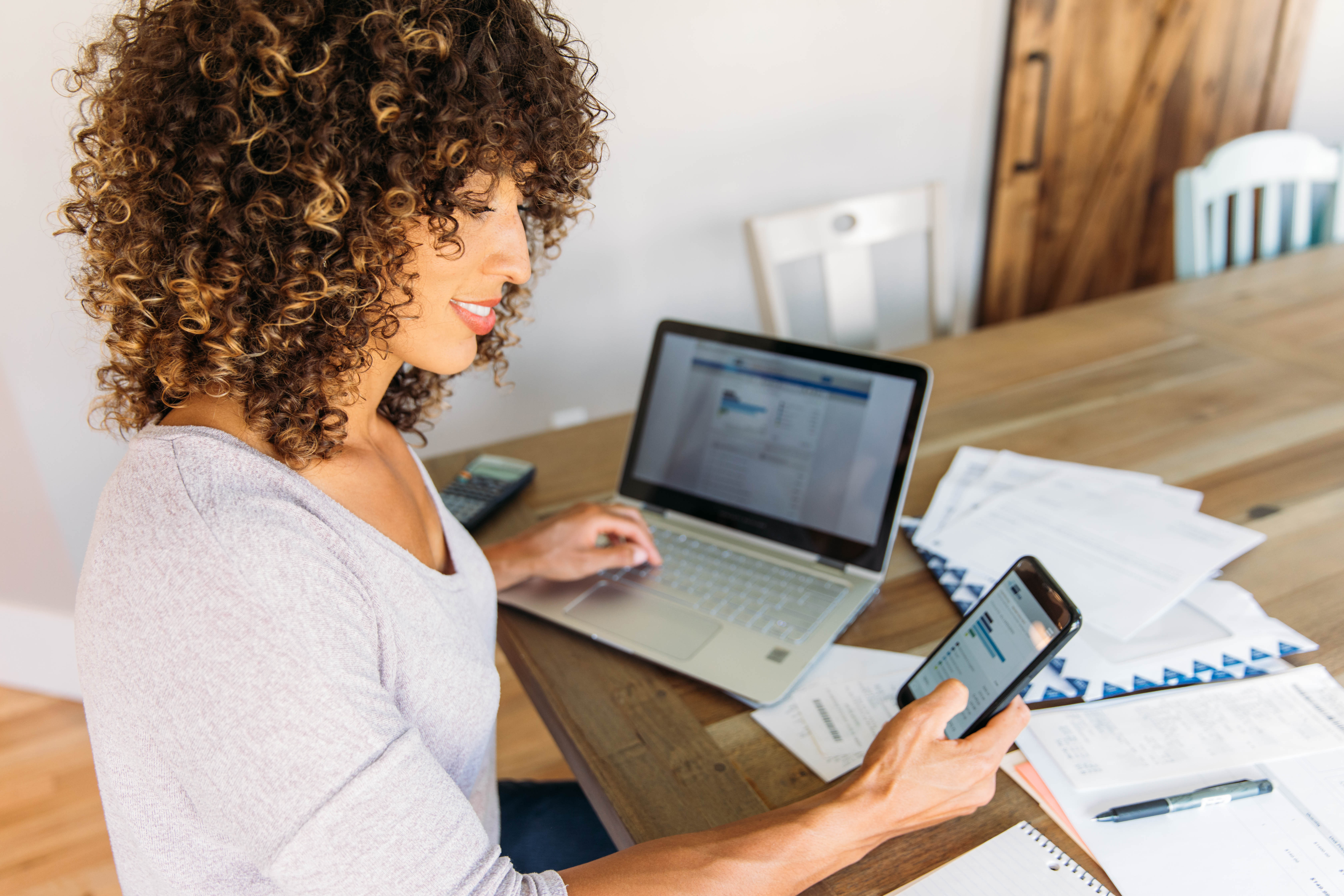 Woman Doing Finances at Home on Smart Phone