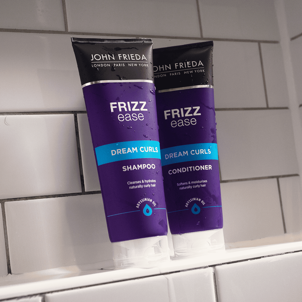 John Frieda Frizz Ease Dream Curls Shampoo and Conditioner on a bathroom shelf