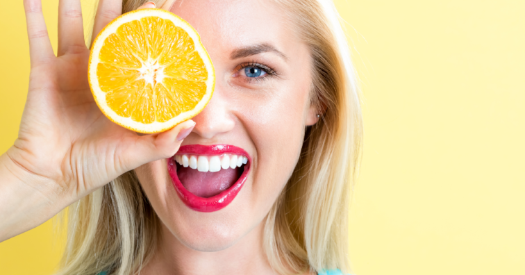 Happy young woman holding oranges halves
