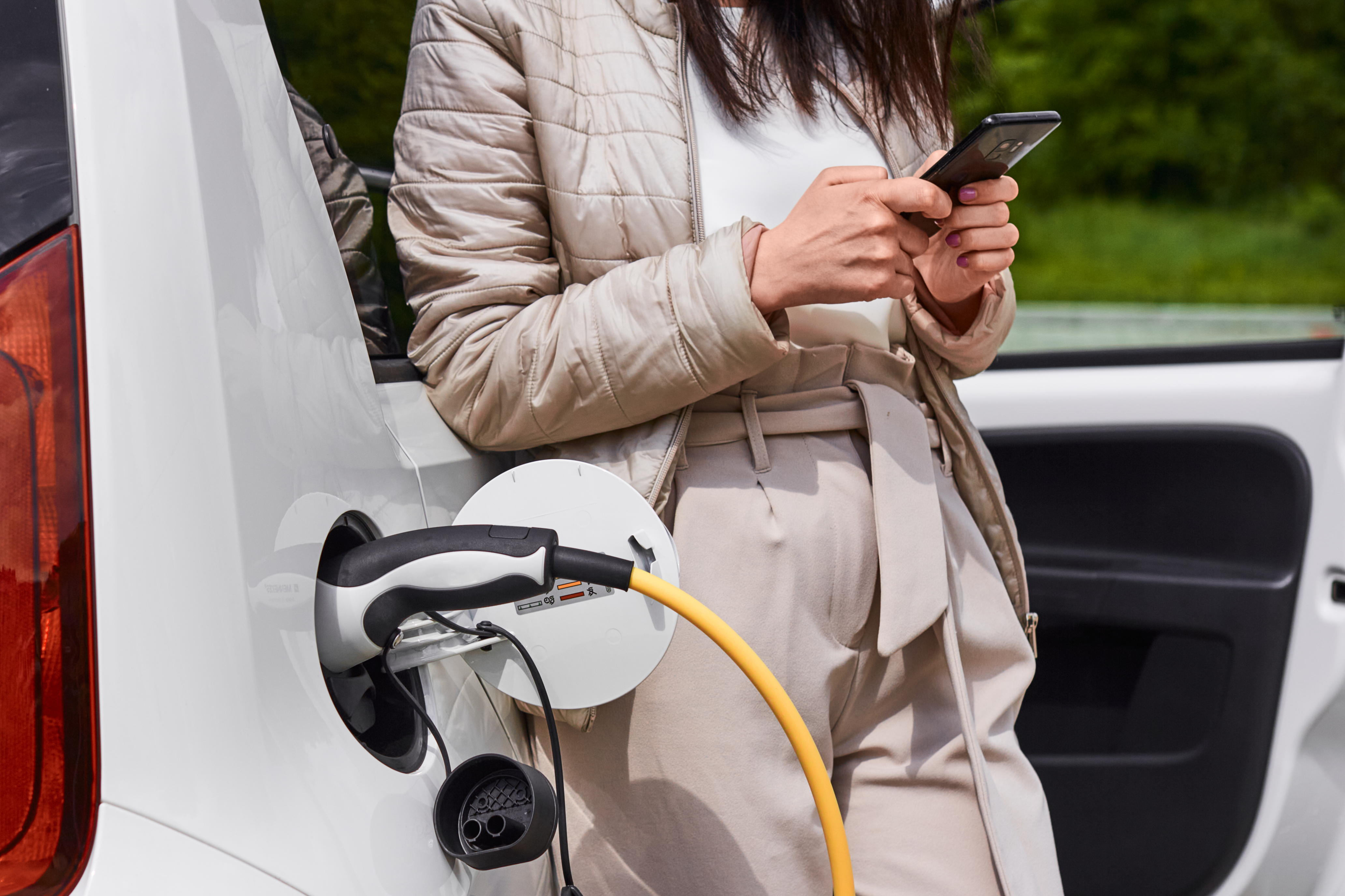 Young woman standing near the electric car with mobile phone in her hand and waiting for recharging of the automobile battery.